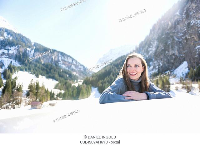 Portrait of smiling young woman leaning on car roof, Bludenz, Austria