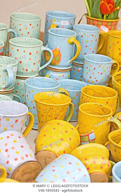 Colorful handcrafted polka-dotted mugs  Colorful gold, lavender and aqua ceramic mugs in a local public market