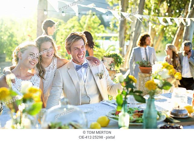 Young couple and bridesmaid during wedding reception in domestic garden