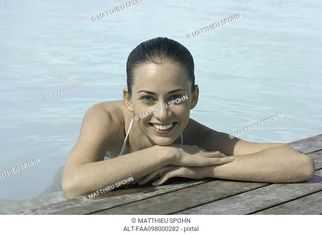 Woman soaking in pool, resting head on arms, portrait