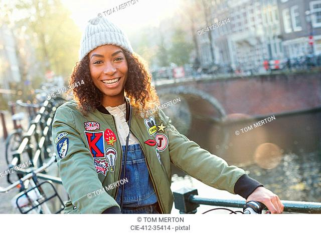Portrait smiling young woman along urban canal, Amsterdam
