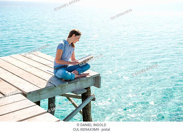 Mid adult woman sitting cross legged on pier, reading magazine