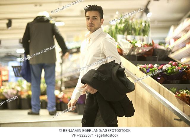 young man in flower store, in Munich, Germany