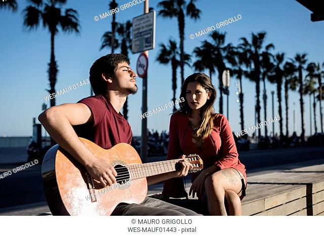 Spain, Barcelona, couple with a guitar sitting on a bench at seaside promenade