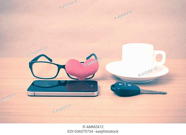 coffee,phone,eyeglasses and car key on wood table background vintage style