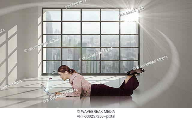 Pretty woman lying on floor and looking at e-shopping offer on laptop