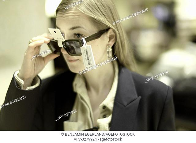 trendy woman trying sunglasses with price tags in shop, in Paris, France