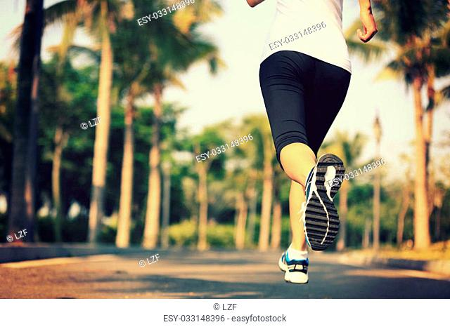Runner athlete running at tropical park. woman fitness jogging workout wellness concept