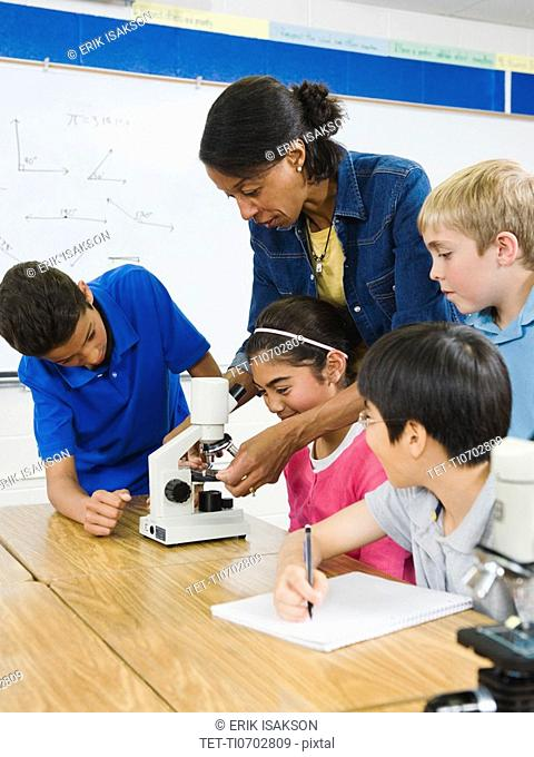 Teacher helping students use microscope in science lab