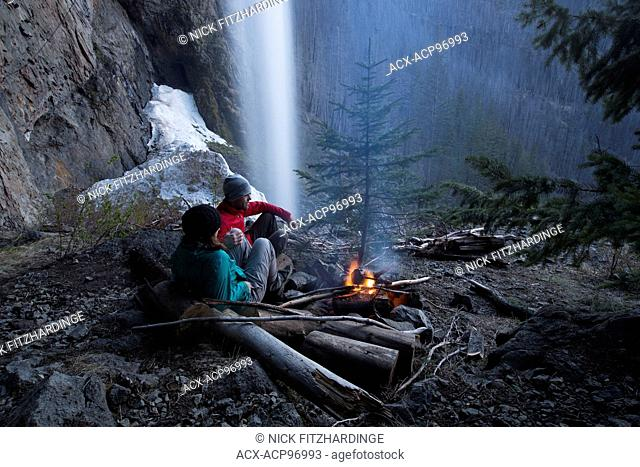 A couple sitting by the fire at Christie Falls, Thompson Okanagan Region, British Columbia, Canada