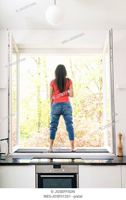 Woman standing in kitchen on windowsill