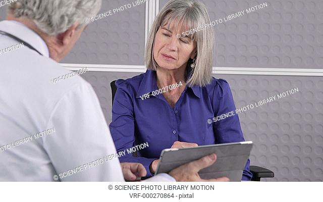 MODEL RELEASED. Senior male doctor using digital table in a consultation with senior female patient