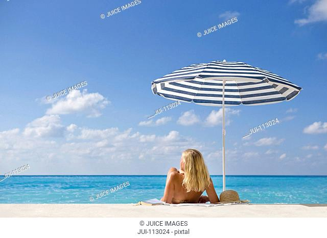 Woman laying on sunny beach under striped beach umbrella