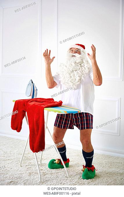 Santa claus with iron board and flat iron