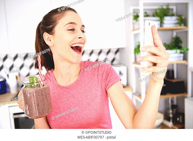 Portrait of laughing young woman with glass of smoothie taking selfie with smartphone in the kitchen