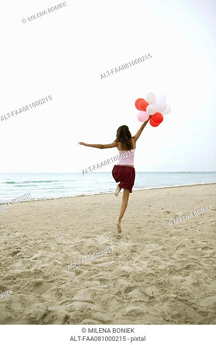 Woman running on beach with bunch of balloons, rear view