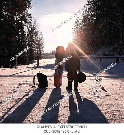 Boy on snow covered landscape holding snowboard
