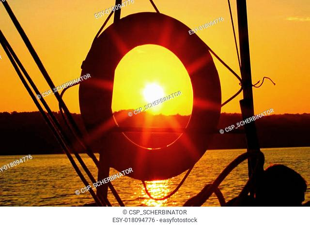 Sunset over the ocean and lifebuoy