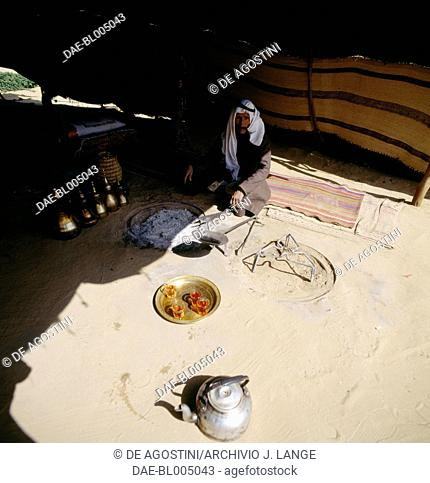 Bedouin man sitting with tea and teapots in a tent, Judean Desert Israel