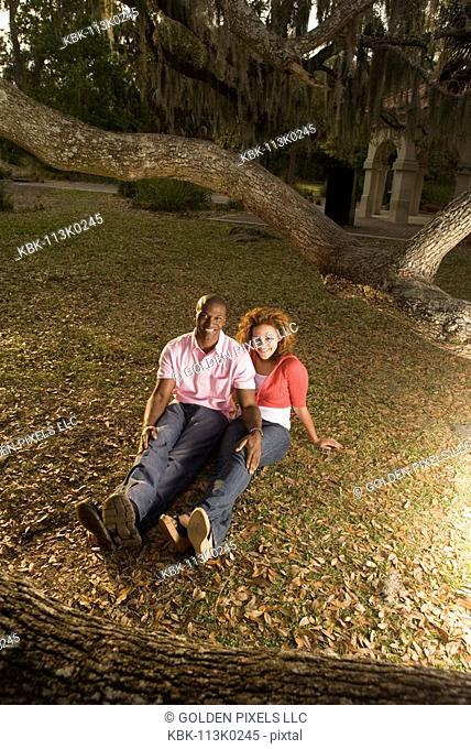 Young multi-ethnic couple sitting on grass amidst oak trees at dusk