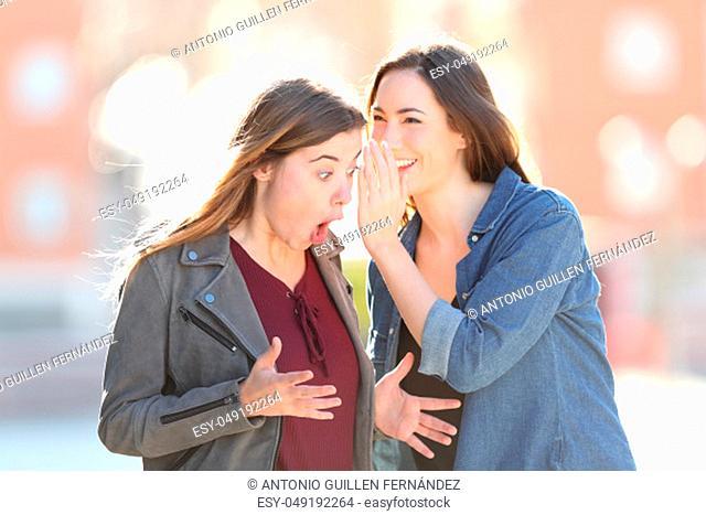 Two gossip girls whispering on ear a secret standing in the street