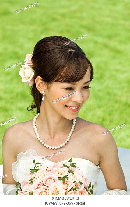 a smiling Japanese bride holding bouquet of flowers