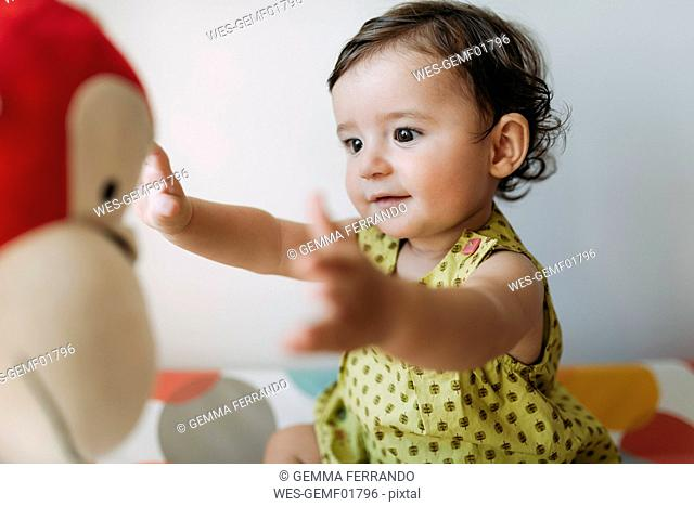 Baby girl playing with a cuddly toy