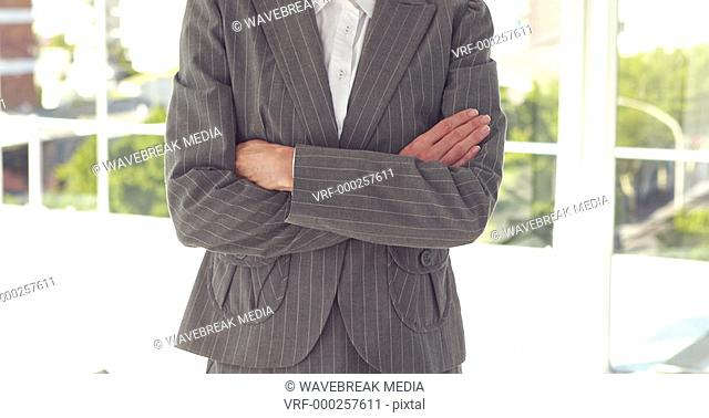 Happy businesswoman smiling at camera with arms crossed