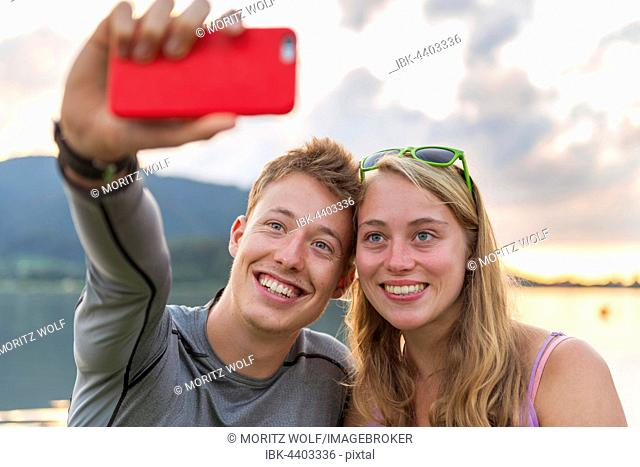 Young couple photographing themselves with mobile phone, selfie, Schliersee, Upper Bavaria, Bavaria, Germany