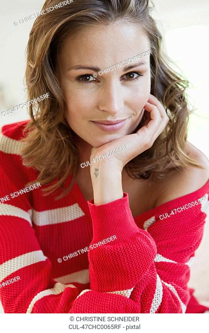 Smiling woman resting chin in hand