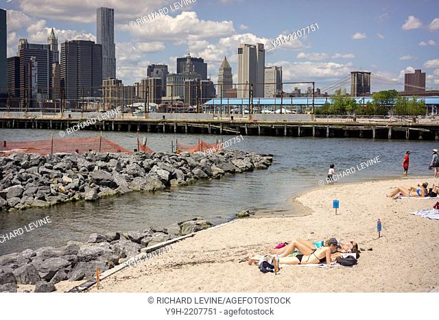 Parkgoers enjoy the newly opened beach by the East River in Brooklyn Bridge Park in Brooklyn in New York. Sunbathing is permitted but swimming or wading is not