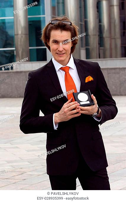 Businessman in a beautiful suit and orange tie shows his award