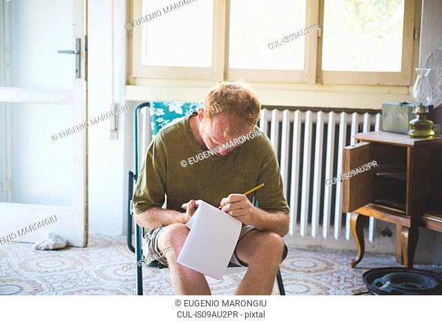 Man writing notes in room