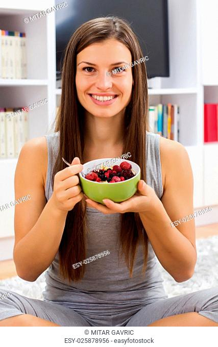 Happy young woman holding cereal with fruits in bowl at home. Healthy Food and Dieting concept