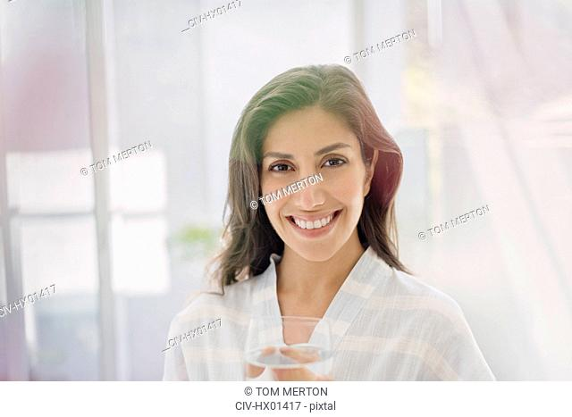 Portrait smiling brunette woman drinking water