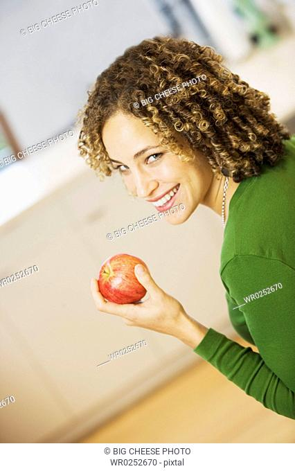 Portrait of woman with apple in kitchen
