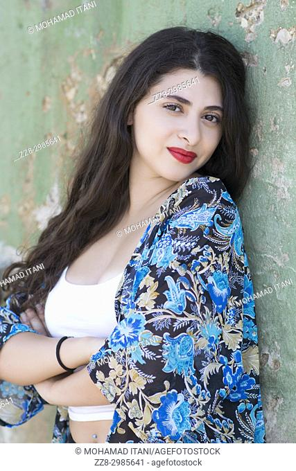Beautiful young woman leaning against the wall arms folded smiling