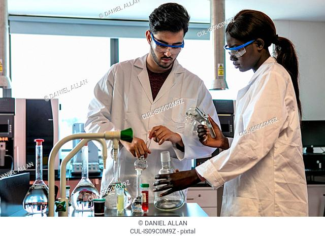 Young male and female scientists preparing experiment with sample bottles in laboratory