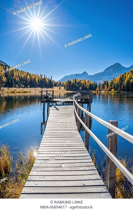 Wooden jetty on mountain lake with sun in autumn, Lake Starz, St. Moritz, Engadin, Grisons, Switzerland