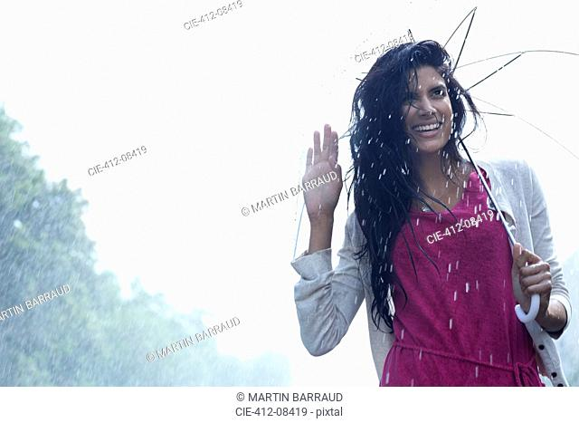 Portrait of smiling woman under umbrella in rain