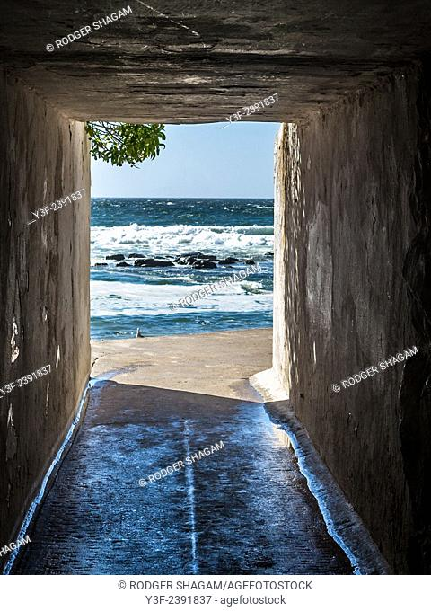 A narrow, dark tunnel leads from a road, under a railway line,  to the beach. St James Tidal Pool, Cape Town, South Africa
