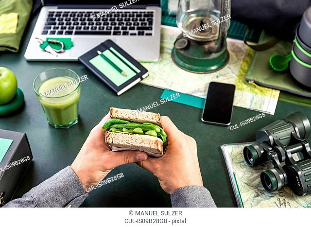 Mans hand's holding sandwich at table with hiking equipment and laptop