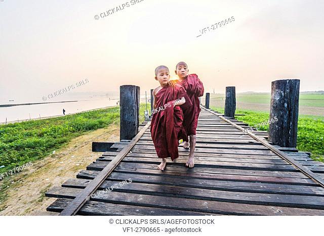 Amarapura, Mandalay region, Myanmar. Monks walking on the U Bein bridge at sunrise