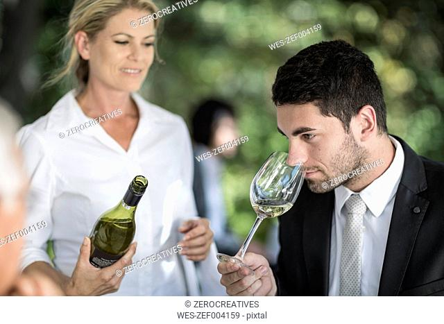 Client in restaurant examining white wine