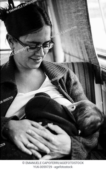 Portrait of mom with baby while nursing, old vintage black and white photograph