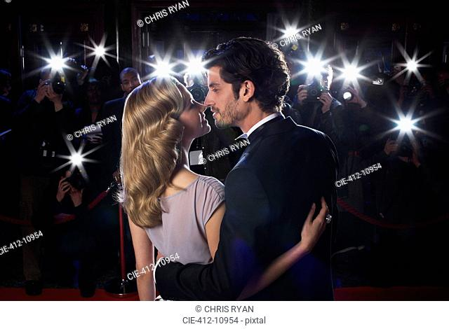 Paparazzi photographing celebrity couple kissing at red carpet event