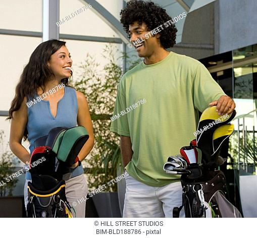 Multi-ethnic couple holding golf bags
