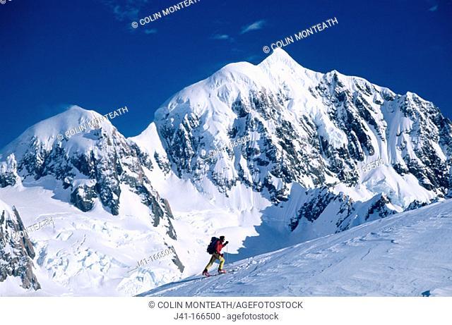 Ski mountaineer near the summit of Von Bulow peak. Mt. Tasman behind. Westland National Park. New Zealand