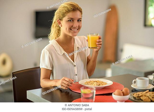 Young woman at breakfast table drinking orange juice
