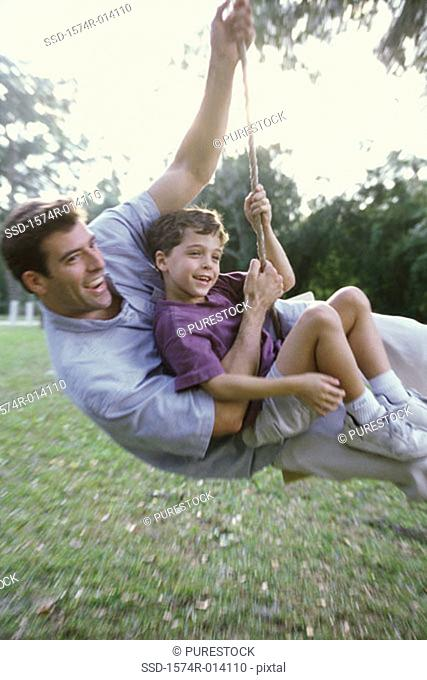 Side profile of a father and son swinging on a rope swing